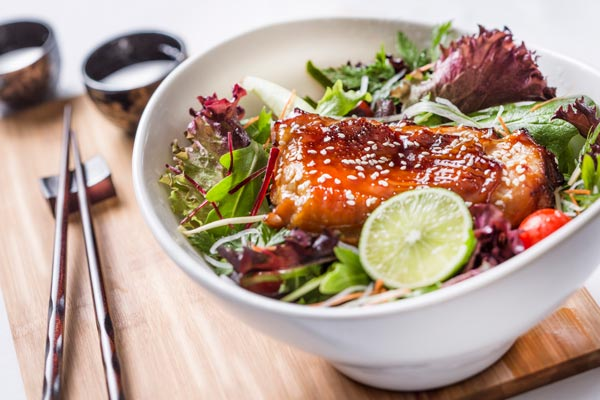 picture of teriyaki chicken with lime, salad and chopsticks